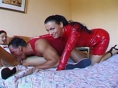 Kinky chick in red latex suit fucks couple
